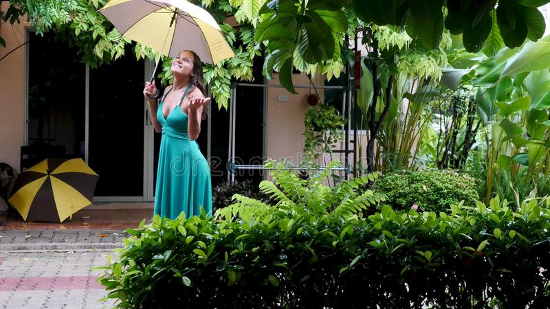 Young beautiful woman in green dress walks in the rain. Hand of women holding an umbrella. royalty free stock images