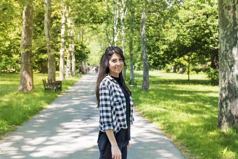 Young Beautiful Woman in a Green Park. Brunette beautiful woman on a walk in a summer parkn royalty free stock photography