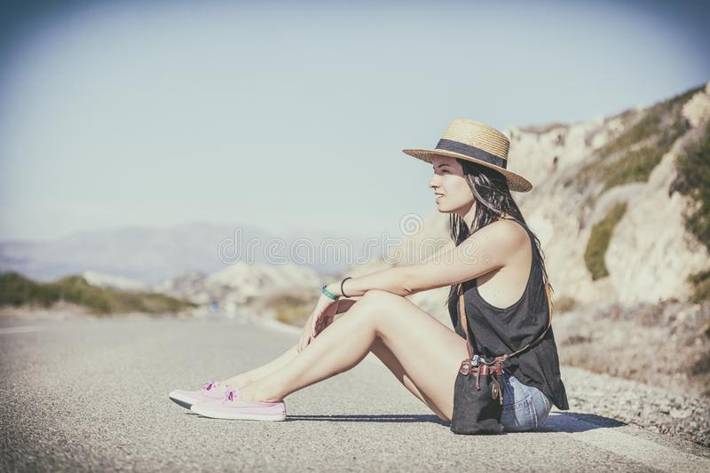 Young beautiful woman in a hat sitting on the road against the b. Ackdrop of beautiful landscape stock photography