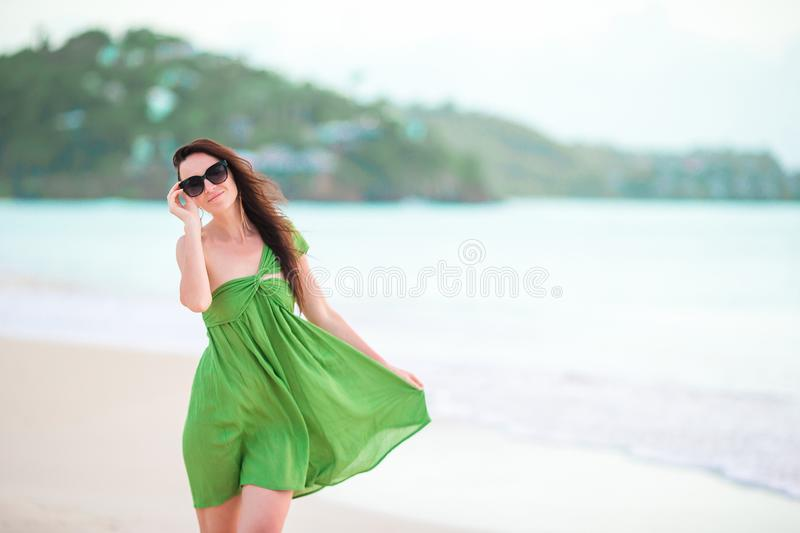 Young beautiful woman having fun on tropical seashore. Happy girl walking at white sand tropical beach stock image