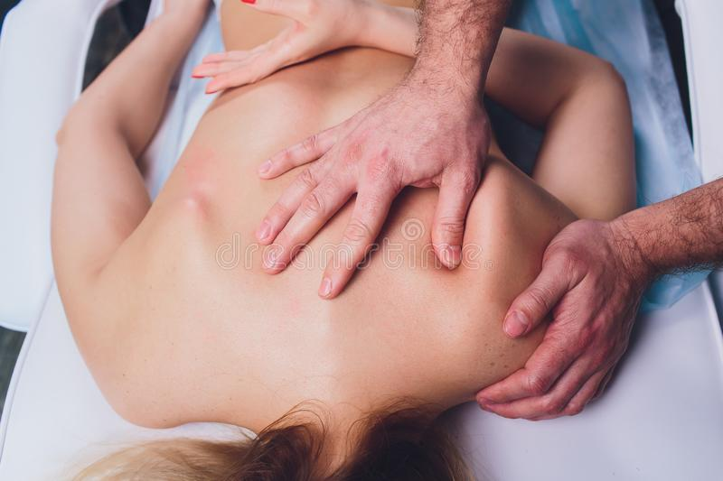 Young beautiful woman having massage in spa salon Physiotherapis. royalty free stock image
