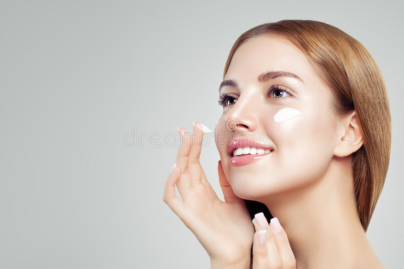 Young beautiful woman with healthy clear skin applying moisturizing cream on her face. Female face closeup royalty free stock images