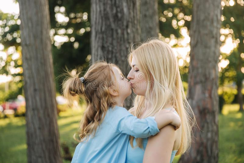 Young beautiful woman with her little cute daughter. Young daughter hugs mother in summer park. Kiss mom royalty free stock photography