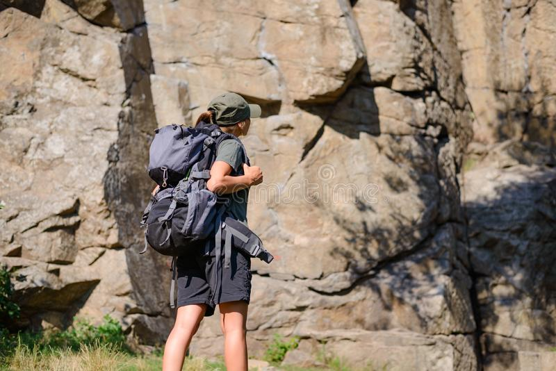 Young Beautiful Woman Hiker with Big Backpack on the Rock Background. Adventure and Travel Concept stock images