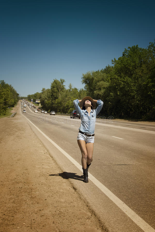 Young beautiful woman hitchhiking along a road. Young beautiful woman in short shorts hitchhiking along a road stock photography