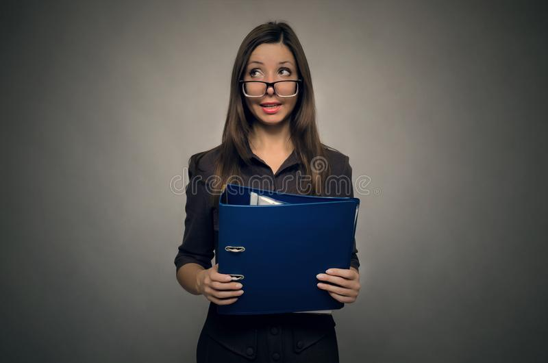 Teacher or secretary woman. Young beautiful woman holding in hands the documents folder in front of herself. Silly secretary. Documentation work. Office stock photo