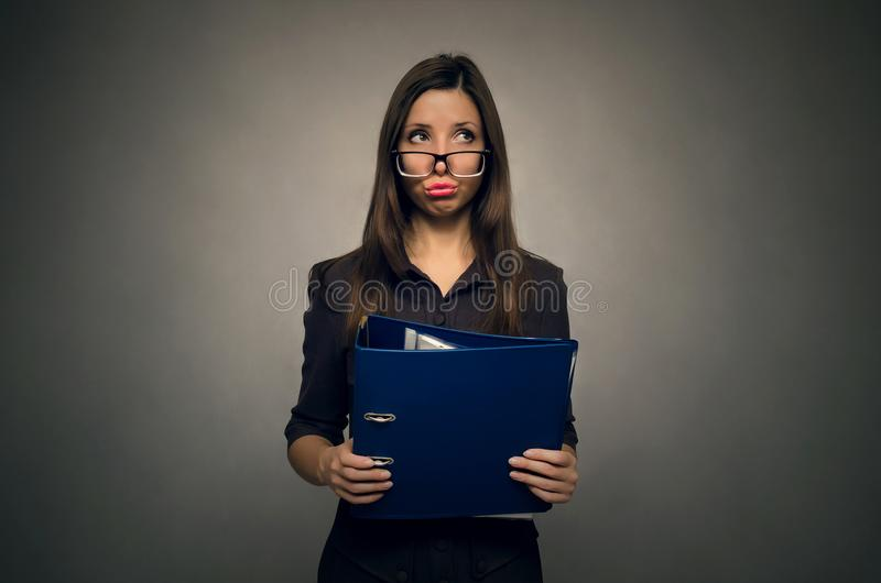 Teacher or secretary woman. Young beautiful woman holding in hands the documents folder in front of herself. Silly secretary. Documentation work. Office stock photography