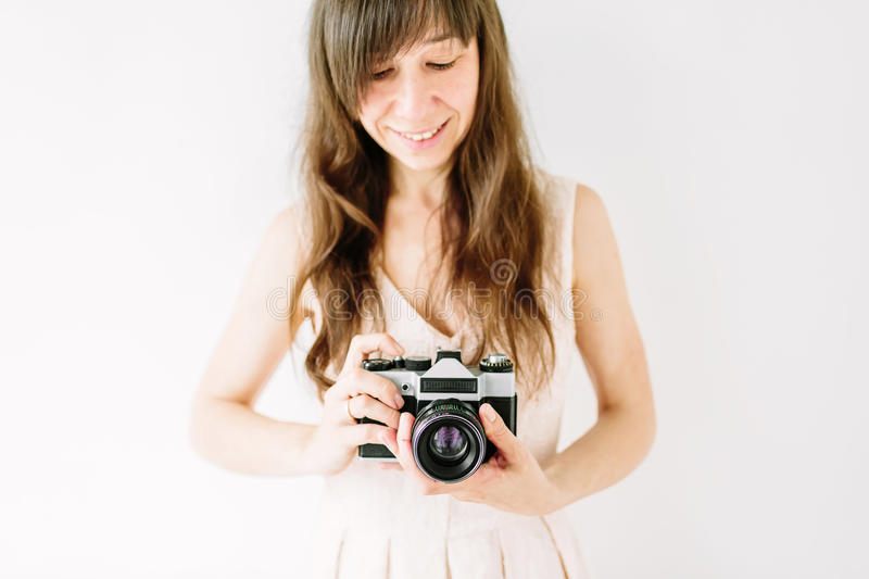 Young beautiful woman holding in hands old vintage film camera. Girl wedding photographer royalty free stock photography