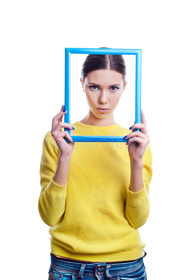 Young beautiful woman holding light blue frame with sad expression. Isolated on white background stock photo