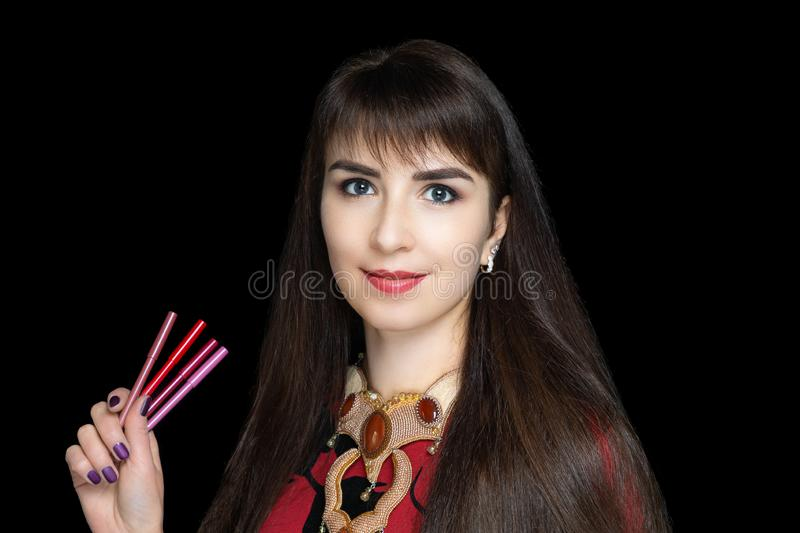 Young beautiful woman holding lip pencils. Consultant cosmetics store. Professional set to create customer ideas. Long hair brunette fringe. Ready to work make stock photography