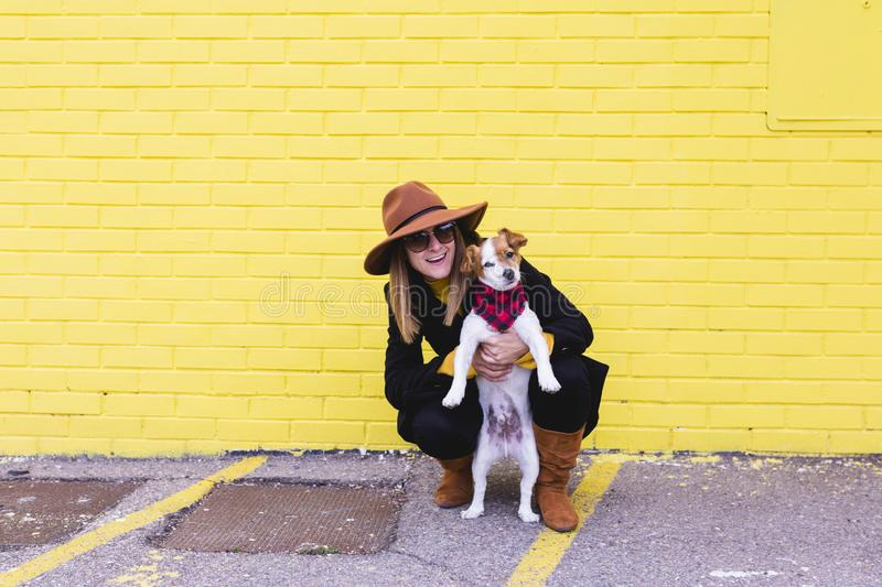Young beautiful woman holding and loving her dog. Yellow brick wall background. Love and pets outdoors stock photos