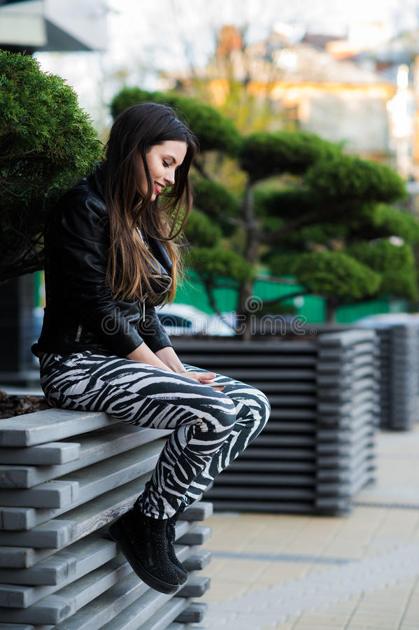 Young beautiful woman holding mobile phone in hand and sitting on the bench in the city park royalty free stock image