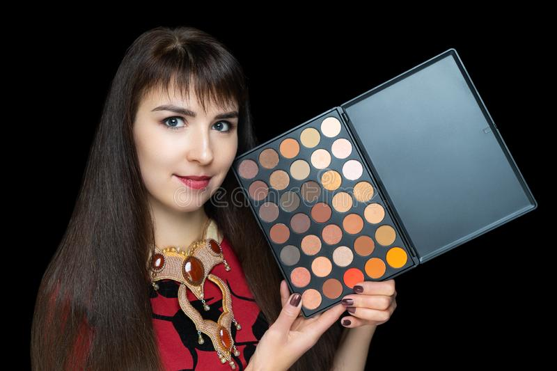 Young beautiful woman holding plastic palette multi-colored shadows royalty free stock photography