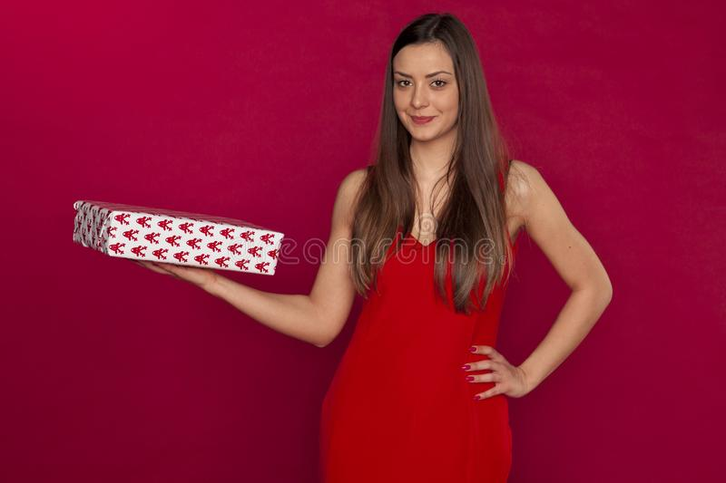 Young beautiful woman holding a small gift, copy space above her royalty free stock image