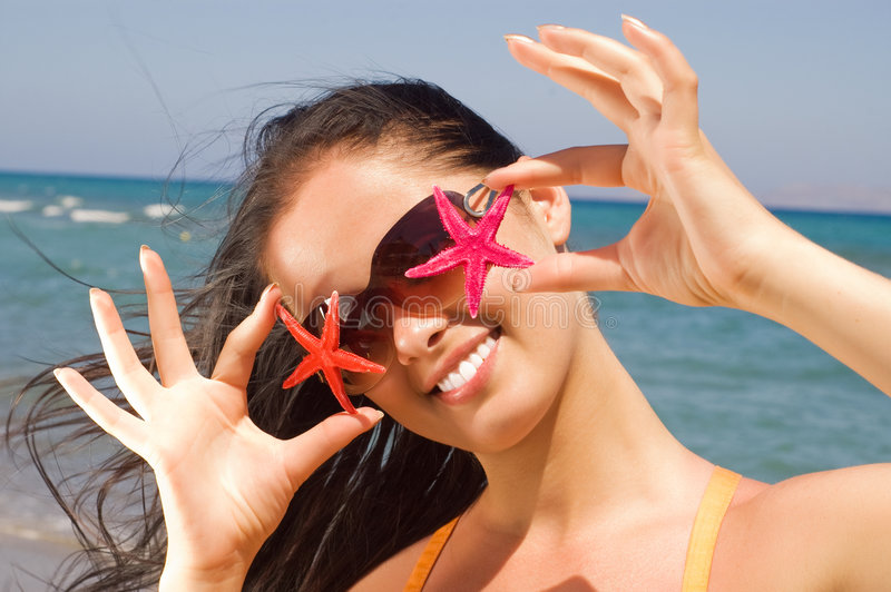 Young beautiful woman holding two starfish royalty free stock image