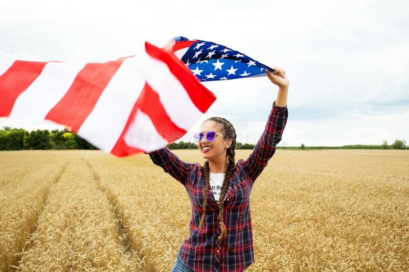 Young beautiful woman holding USA flag. On the field royalty free stock images
