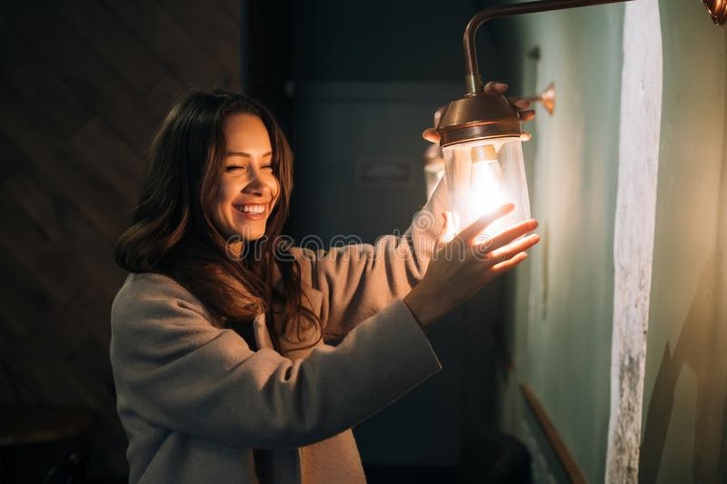 Young beautiful woman holds in her hand a small wall lamp royalty free stock images