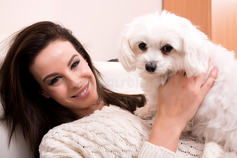 Young beautiful woman hugging her puppy. A young, beautiful woman hugging her cute little puppy royalty free stock photography
