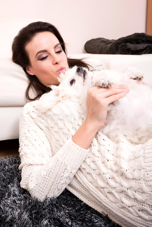 Young beautiful woman hugging her puppy. A young, beautiful woman hugging her cute little puppy royalty free stock photo