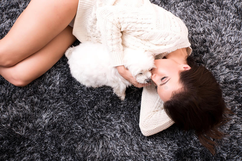 Young beautiful woman hugging her puppy. A young, beautiful woman in underwear lying on the carpet and hugging her cute little puppy royalty free stock images