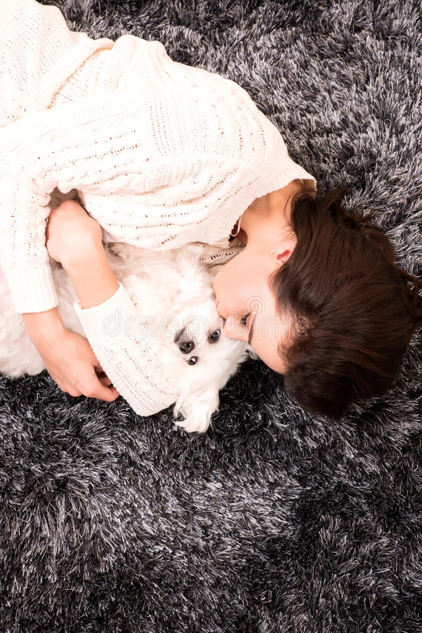 Young beautiful woman hugging her puppy. A young, beautiful woman in underwear lying on the carpet and hugging her cute little puppy stock photos