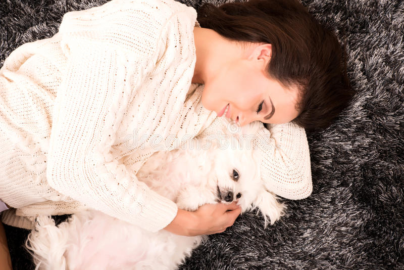 Young beautiful woman hugging her puppy. A young, beautiful woman in underwear lying on the carpet and hugging her cute little puppy royalty free stock photos