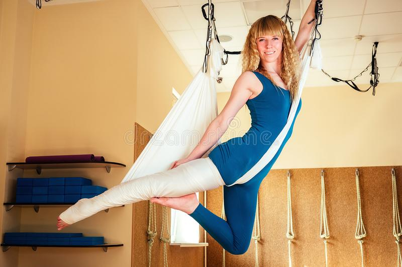 Young and beautiful woman instructor practicing yoga on canvases. antigravity yoga in the gym. yoga on hammocks and royalty free stock image