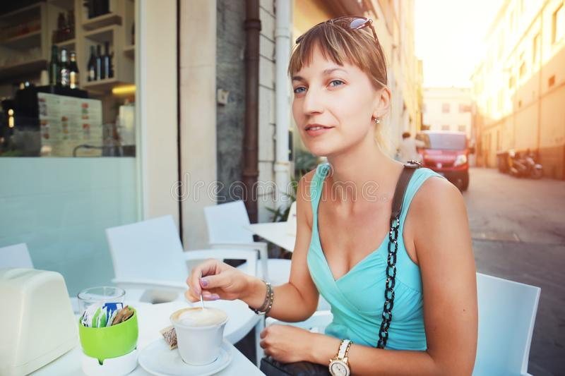 Young beautiful  woman at italian street cafe enjoying drinking coffee in Rome. Pretty girl having breakfast in morning in royalty free stock photography