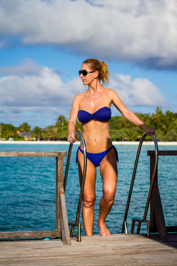 Young beautiful woman on a jetty, tropical vacation. Maldives beach with a young woman panorama. Luxury water villas, in exotic blue lagoon. Full screen screen royalty free stock photography