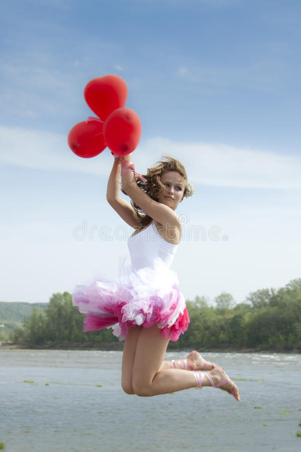Young beautiful woman jumping with balloons. stock photos