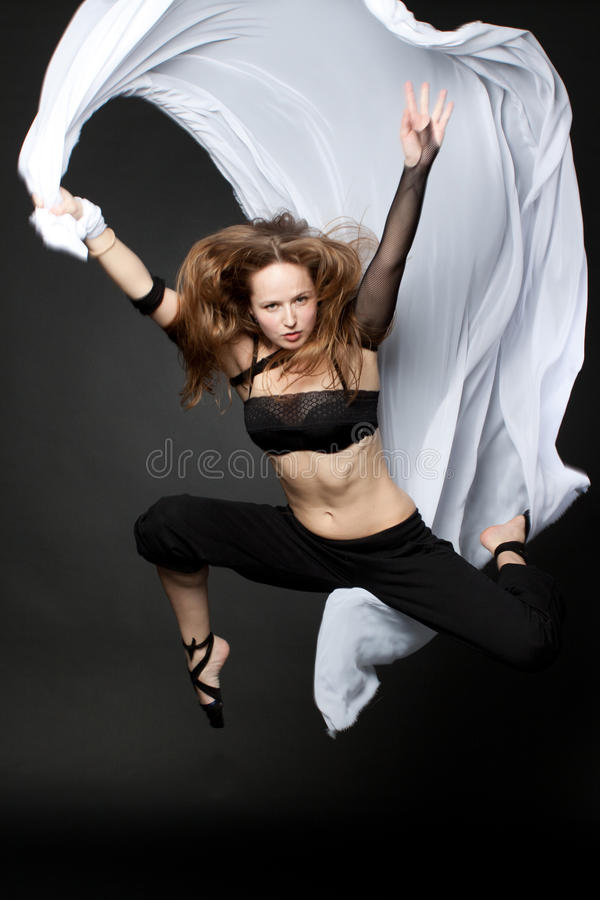 Young beautiful woman jumping on an black royalty free stock images