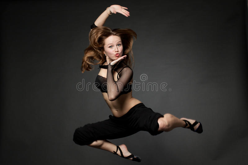 Young beautiful woman jumping on an black royalty free stock photography