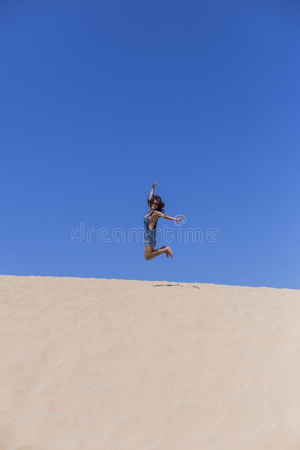 Young beautiful woman jumping on the dunes in Portugal. Summertime, fun and holidays concept. High, forward, healthy, vitality, run, looking, valley, dry royalty free stock photos