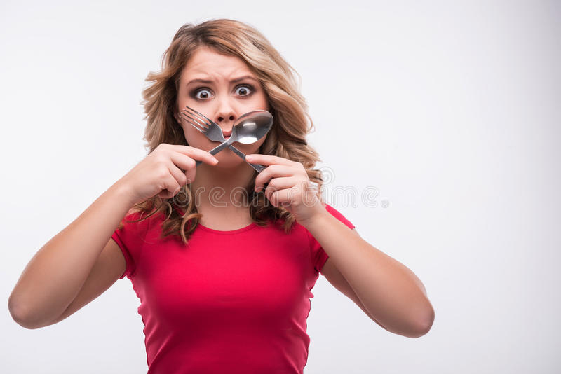 Young beautiful woman with knife and fork crossed. Half-length portrait of young beautiful woman with knife and fork crossed at mouth, diet concept, on white royalty free stock photo
