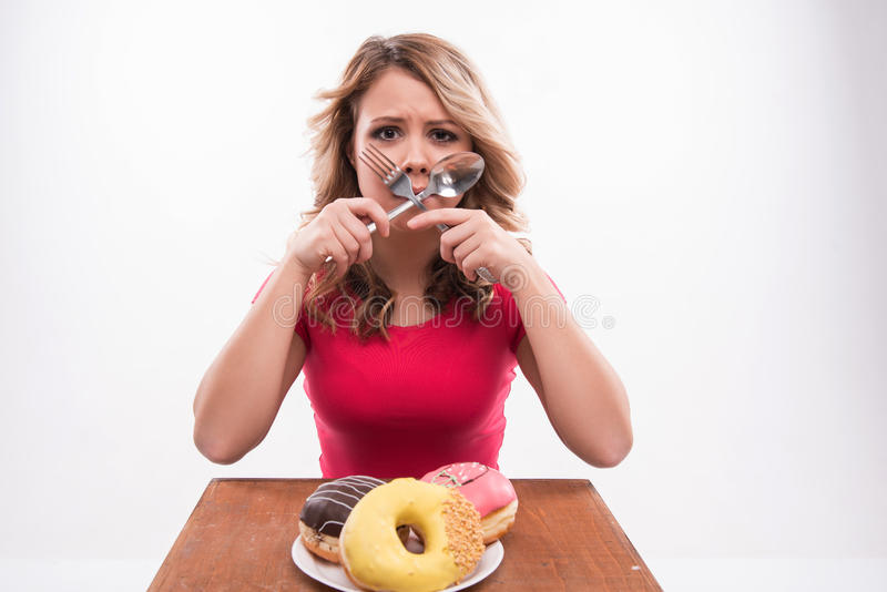 Young beautiful woman with knife and fork crossed. At mouth sitting in front of doughnuts, diet concept, on white background stock photo
