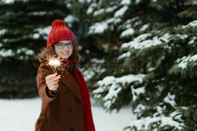 Young beautiful woman in knitted red hat and scarf standing in the park with bengal light, sparkler. Concept celebration royalty free stock images