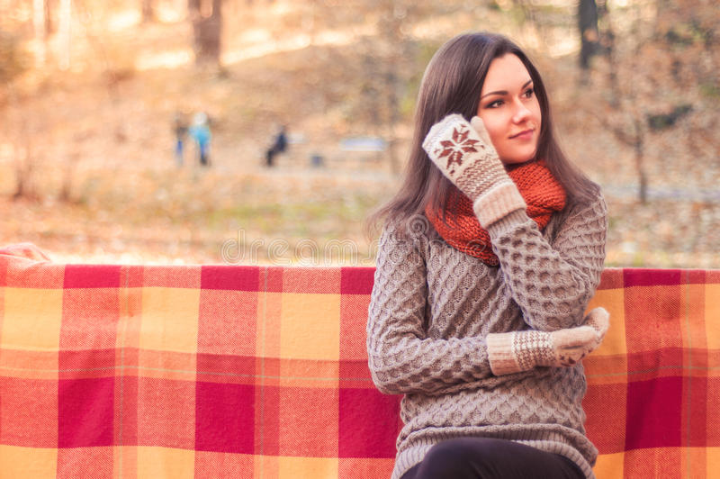 Young beautiful woman in a knitted sweater sitting on a bench in an autumn park stock photo