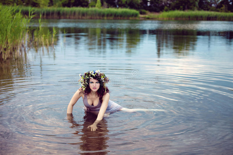 Young beautiful woman in the lake water. Young beautiful drowned woman in gey dress lying in the water royalty free stock image
