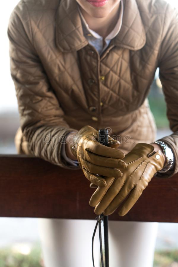 Gloved hands closeup. Young beautiful woman in leather gloves at stable royalty free stock photography