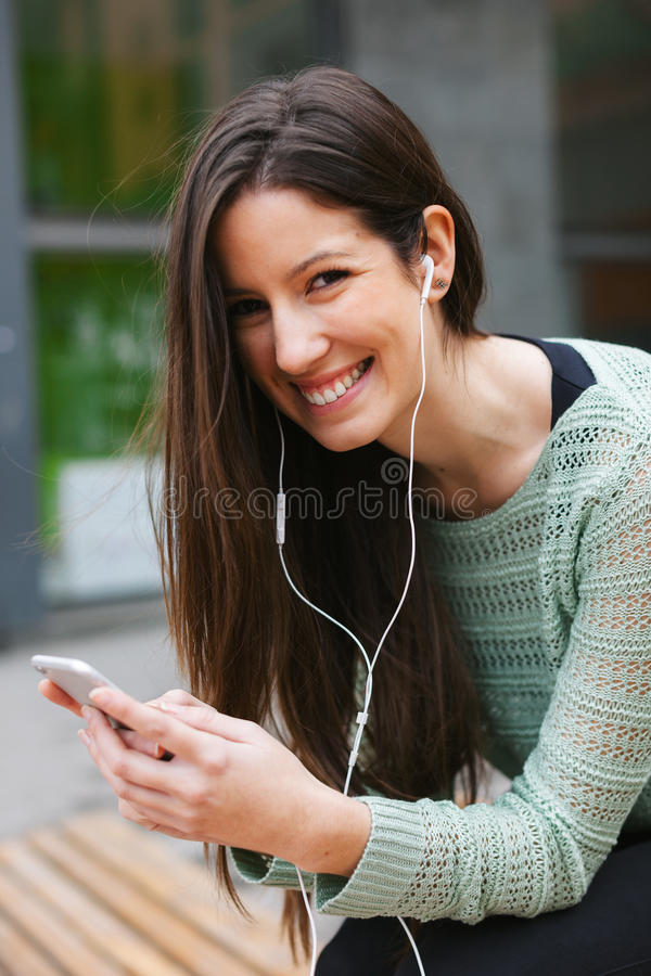 Young beautiful woman listening to music with phone in outdoors. stock images