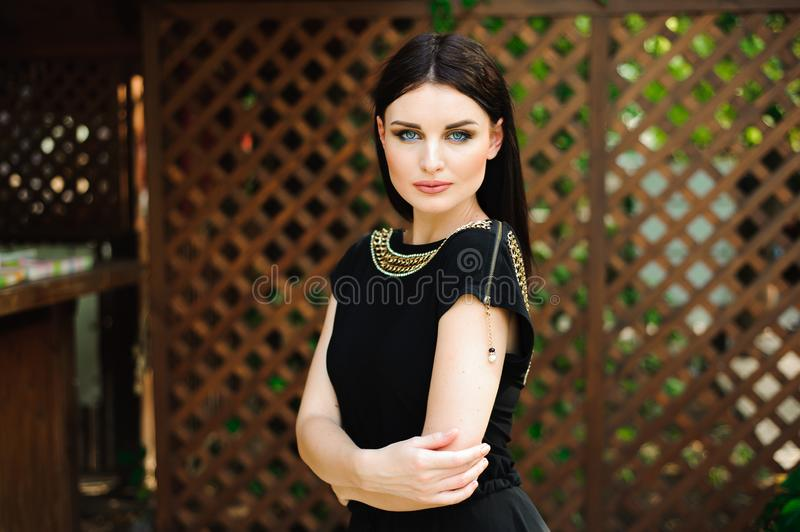 Young beautiful woman in long black evening dress walking path in park. Fashion style portrait of gorgeous beautiful royalty free stock images