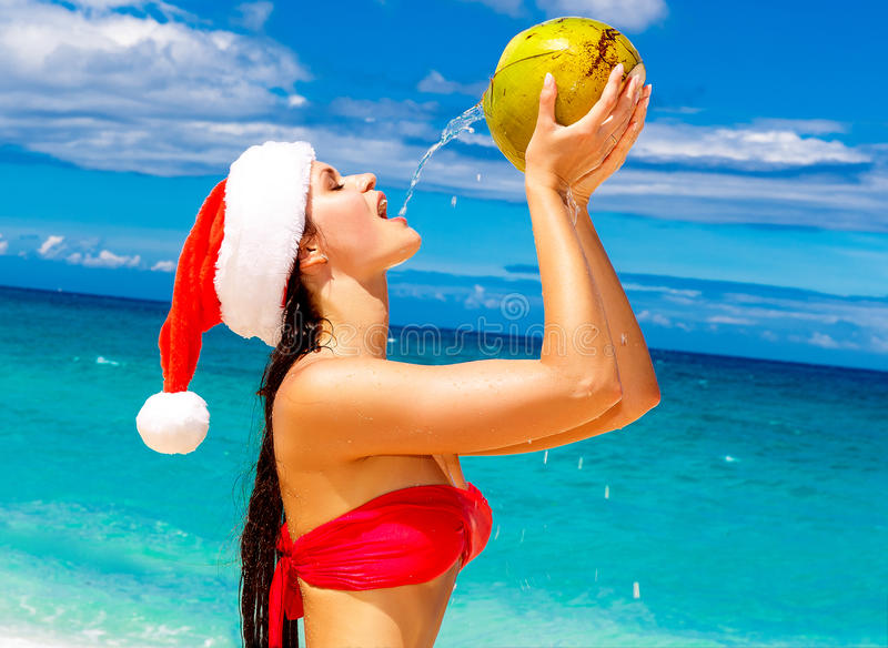 Young beautiful woman with long black hair in red bikini, dressed in red Santa Claus hat is drinking coconut water on tropical be. Ach. Christmas and New Year on royalty free stock photography