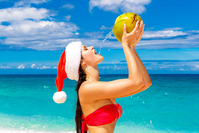 Young beautiful woman with long black hair in red bikini, dressed in red Santa Claus hat is drinking coconut water on tropical be. Ach. Christmas and New Year on stock images