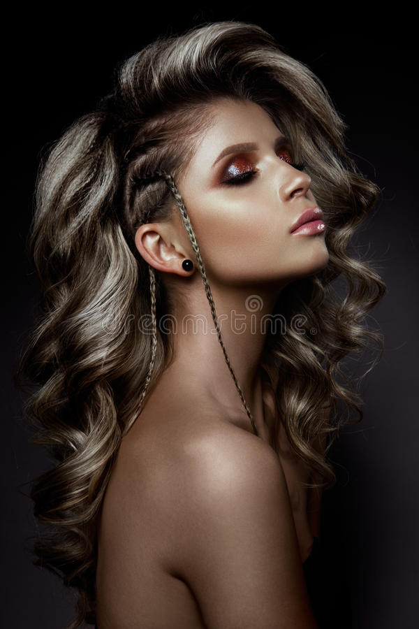 Young beautiful woman with long curly hairs. And colored make up stock photos