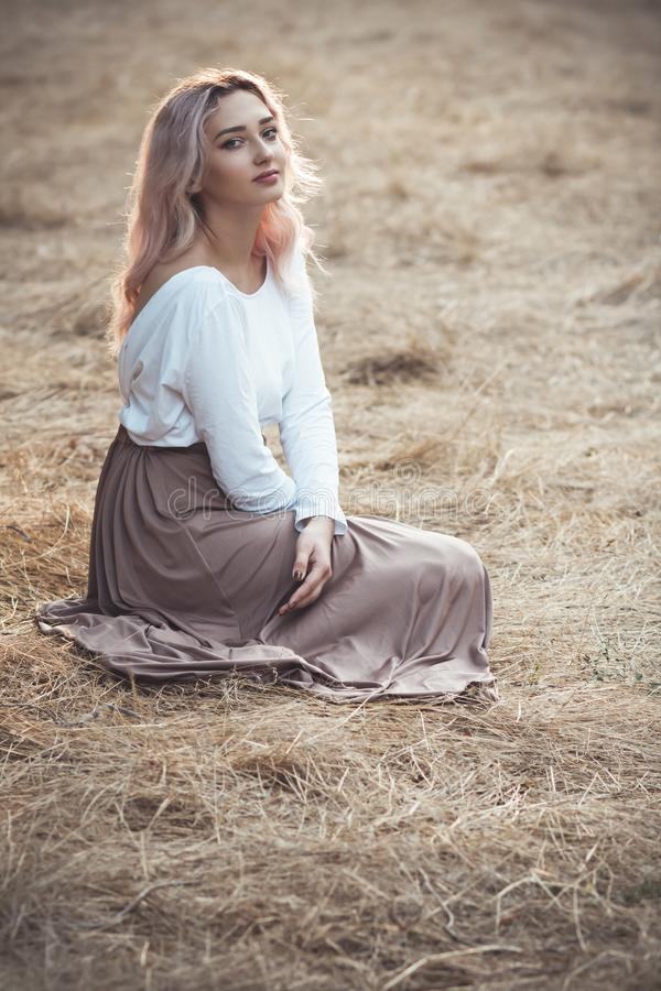 Young beautiful woman in a long dress on a background of dry grass sitting on glade in the forest, romantic girl relaxing alone in royalty free stock photography