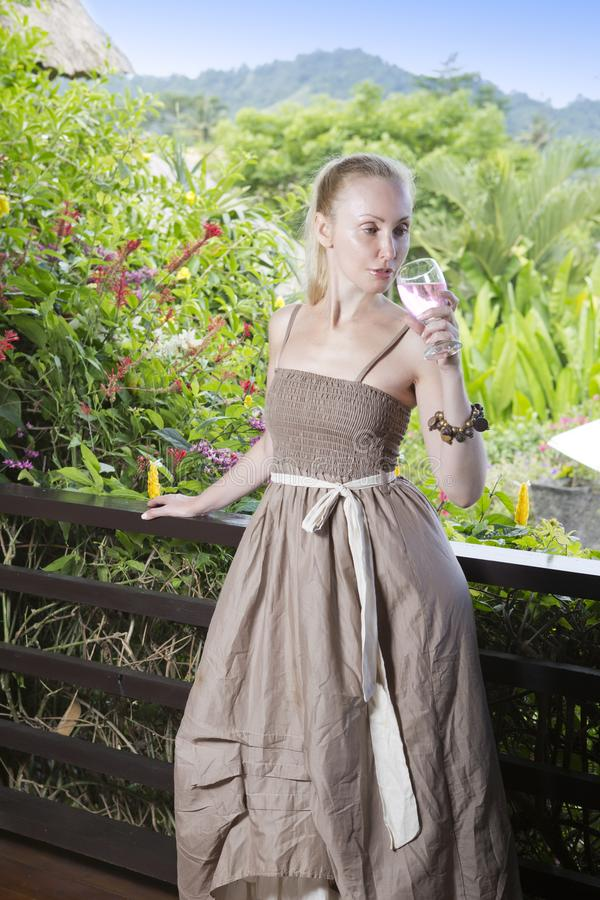 The young beautiful woman in a long dress with a glass of wine looks at the tropical nature stock images