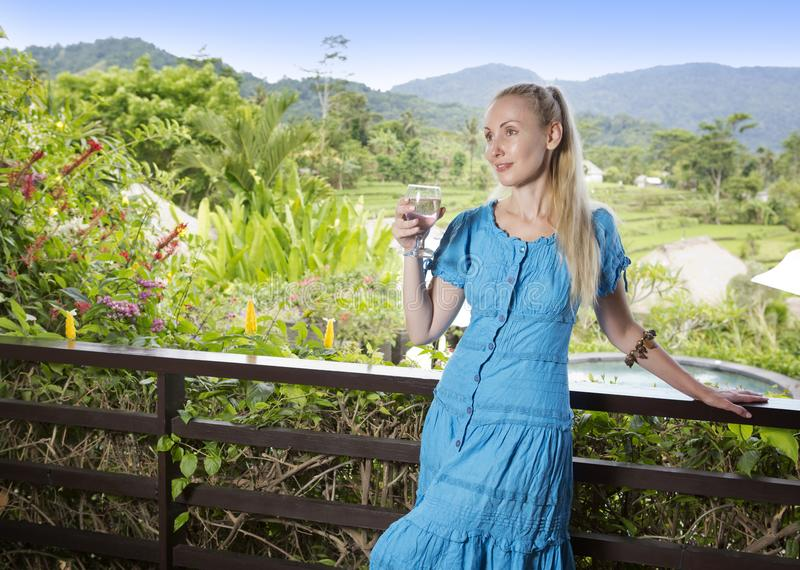 Young beautiful woman in a long dress with a glass of wine looks at the tropical nature stock images