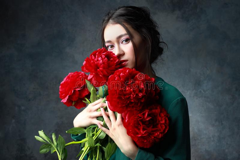 Young beautiful woman with long hair in a green dress with a big bouquet of peonies stock photo