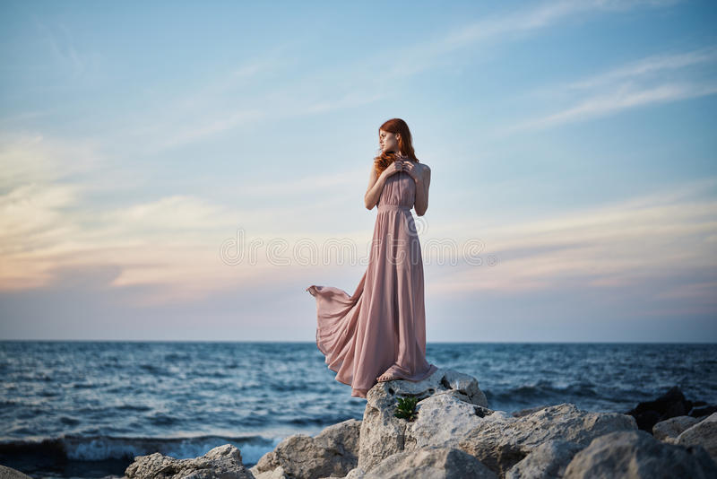Young beautiful woman in a long pink dress is standing on stones on the seashore royalty free stock images