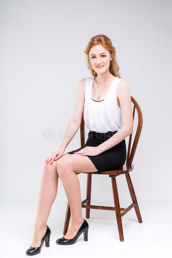 Young beautiful woman with long red, curly hair sitting on a wooden chair on a white background in the studio. Dressed in a white stock photo